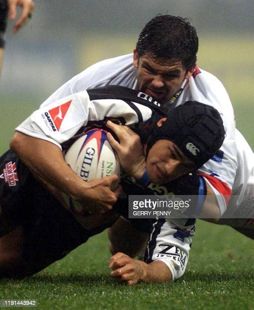 New Zealand's Left Centre Willie Talau is brought down by England's captain and Loose Forward Andrew Farrell 18 November 2000, during their Rugby...