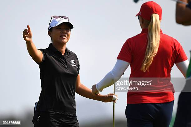 New Zealand's Lydia Ko slautes Britain's Charley Hull during the Women's individual stroke play at the Olympic Golf course during the Rio 2016...