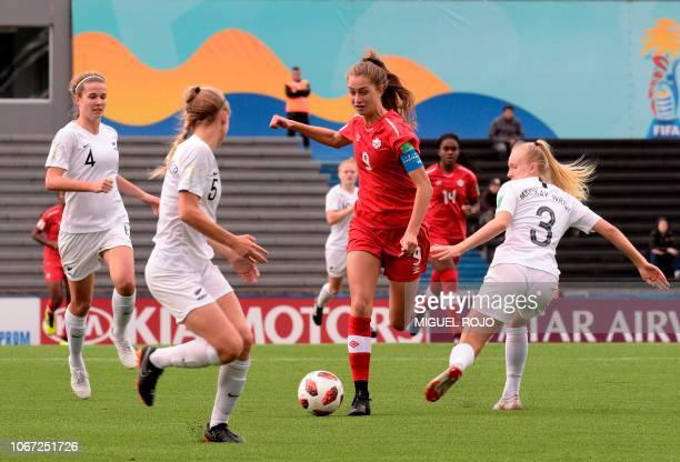 New Zealand's Marisa Van der Meer and Hannah MackayWright vie for the ball with Canada's Jordyn Huitema in the U17 Women's World Cup football match...
