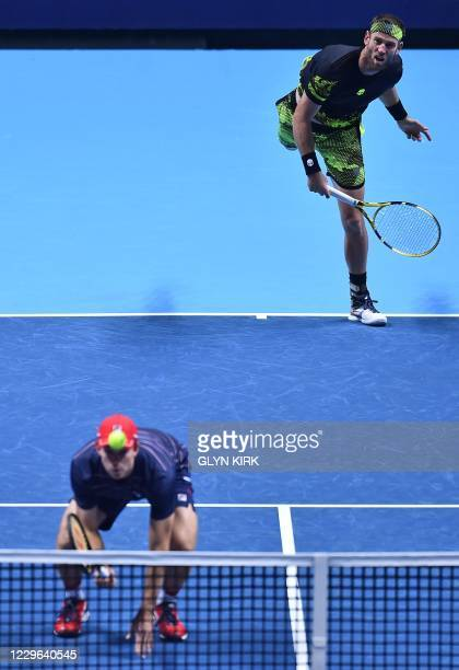 New Zealand's Michael Venus serves while playing with Australia's John Peers against Spain's Marcel Granollers and Spain's Horacio Zeballos in their...