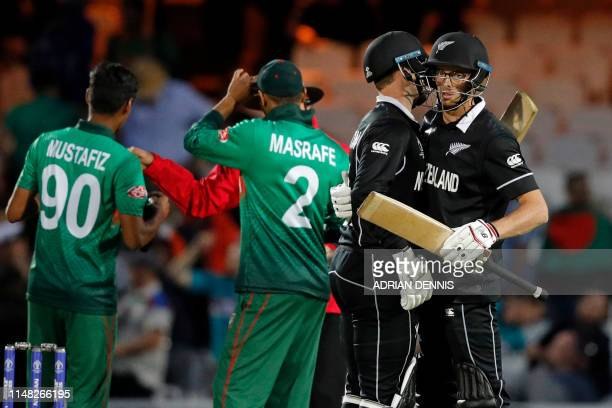 New Zealand's Mitchell Santner and New Zealand's Lockie Ferguson celebrate after the 2019 Cricket World Cup group stage match between Bangladesh and...