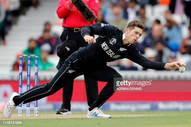 New Zealand's Mitchell Santner fields off his own bowling during the 2019 Cricket World Cup group stage match between Bangladesh and New Zealand at...