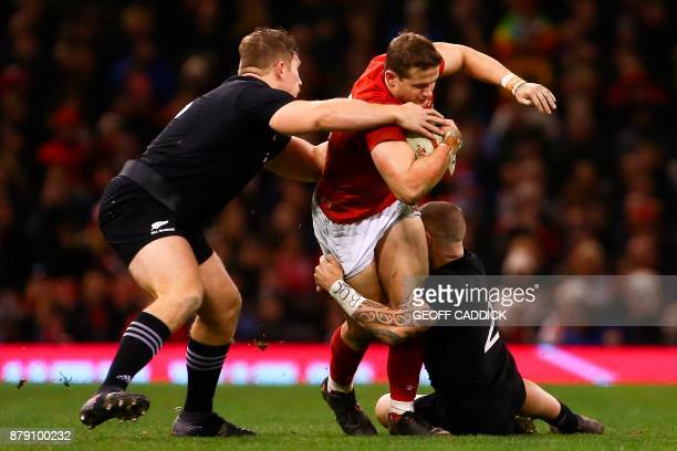 New Zealand's Nathan Harris and New Zealand's TJ Perenara tackle Wales' wing Liam Williams during the Autumn international rugby union Test match...