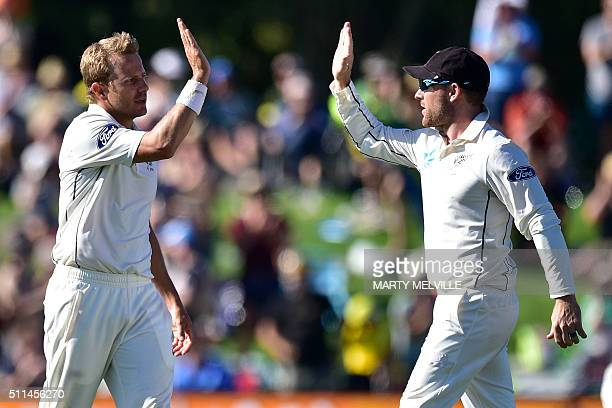 New Zealand's Neil Wagner celebrates Australia's Joe Burns being caught with teammate captain Brendon McCullum during day two of the second cricket...