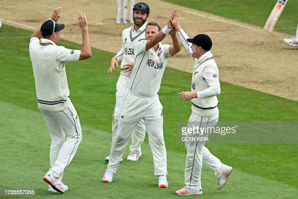 New Zealand's Neil Wagner celebrates with teammates after taking the wicket of India's Ajinkya Rahane for 49 runs during play on the third day of the...