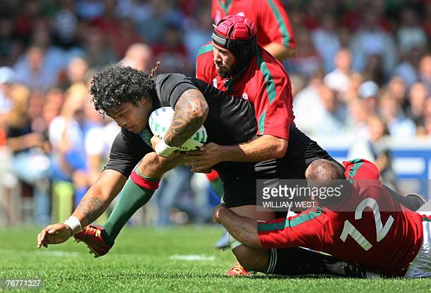 New Zealand's number 8 Sione Lauaki is tackled by Portugal's centre Diogo Mateus during their rugby union World Cup group C match NewZealand vs...