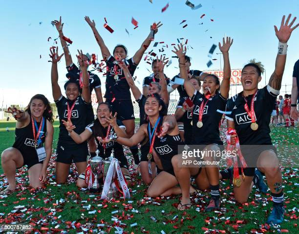 New Zealand's players pose with their medals and the trophy as they celebrate after victory in the women's rugby seven's World series final match...