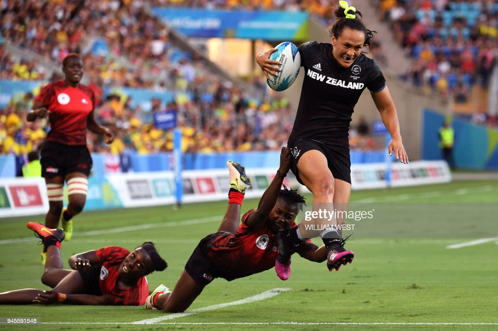 New Zealand's Portia Woodman (R) leaps over Kenya's defenders to score a try in their women's rugby sevens match at the Robina Stadium at the 2018 Gold Coast Commonwealth Games on the Gold Coast on April 13, 2018. / AFP PHOTO / WILLIAM WEST / The erroneous mention[s] appearing in the metadata of this photo by WILLIAM WEST has been modified in AFP systems in the following manner: [Portia Woodman ] instead of [Theresa Fitzpatrick ]. Please immediately remove the erroneous mention[s] from all your online services and delete it (them) from your servers. If you have been authorized by AFP to distribute it (them) to third parties, please ensure that the same actions are carried out by them. Failure to promptly comply with these instructions will entail liability on your part for any continued or post notification usage. Therefore we thank you very much for all your attention and prompt action. We are sorry for the inconvenience this notification may cause and remain at your disposal for any further information you may require.