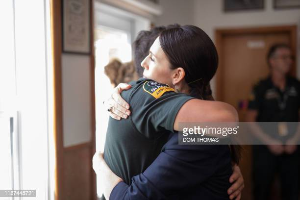 New Zealand's Prime Minister Jacinda Ardern hugs a first responder that helped those injured in the White Island volcano eruption the day before at...