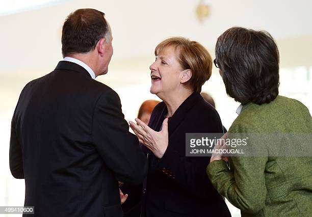 New Zealand's Prime Minister John Key and German Chancellor Angela Merkel chat after addressing a press conference following talks next to an...
