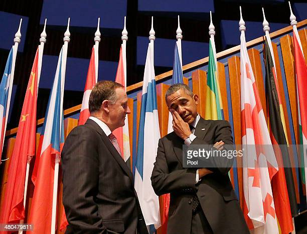New Zealand's Prime Minister John Phillip Key left speaks to US President Barack Obama as he wipes his eye at the closing session of the 2014 Nuclear...