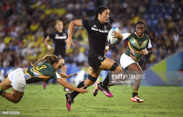 New Zealand's Sarah Goss avoids the tackle of South Africa's Chane Stadler to score in their women's rugby sevens match at the Robina Stadium during...