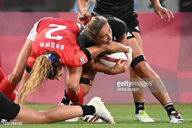 New Zealand's Sarah Hirini fights for the ball with Britain's Abbie Brown during the women's pool A rugby sevens match between the Britain and New...