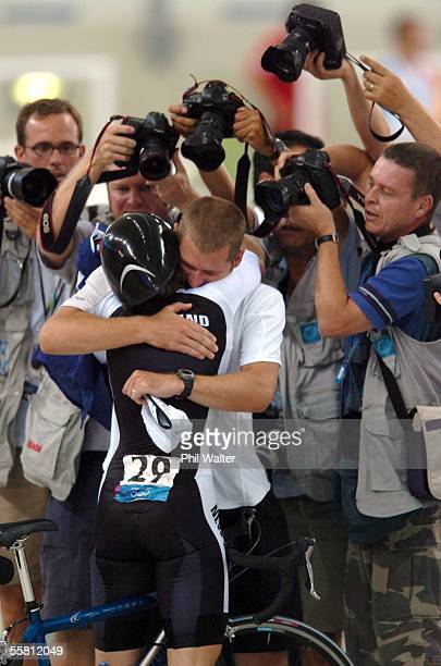 New Zealand's Sarah Ulmer hugs her boyfriend and trainer Brendon Cameron under a photographer scrum after winning the final of the Womens Individual...