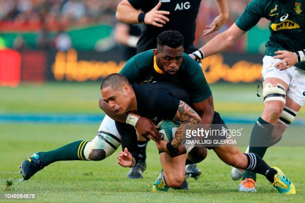 New Zealand's scrum half Aaron Smith is tackled by South Africa's captain Siya Kolisi during the Rugby Championship match between South Africa and...