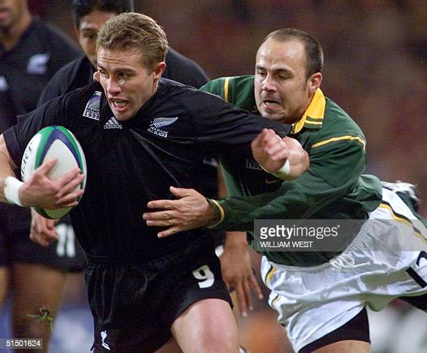 New Zealand's scrumhalf Justin Marshall tries to avoid the tackle of South African center Pieter Muller during the Rugby World Cup third place...
