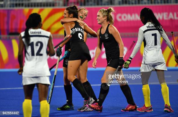 New Zealand's Shiloh Gloyn greets her teammate Amy Robinson for her goal against Ghana during their women's field hockey match at the 2018 Gold Coast...