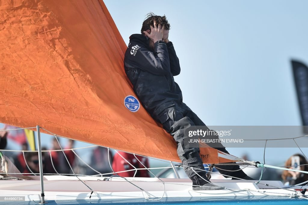New Zealand's skipper Conrad Colman celebrates on his Imoca 60 monohull 'Foresight Natural Energy' upon his arrival in Les Sables-d'Olonne, western France, at the end of the Vendee Globe around-the-world solo sailing race on February 24, 2017. Colman finished 16th. /