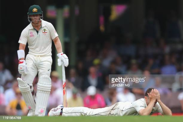 New Zealands Todd Astle reacts after dropping a return catch as Australia's David Warner looks on during the fourth day of the third cricket Test...