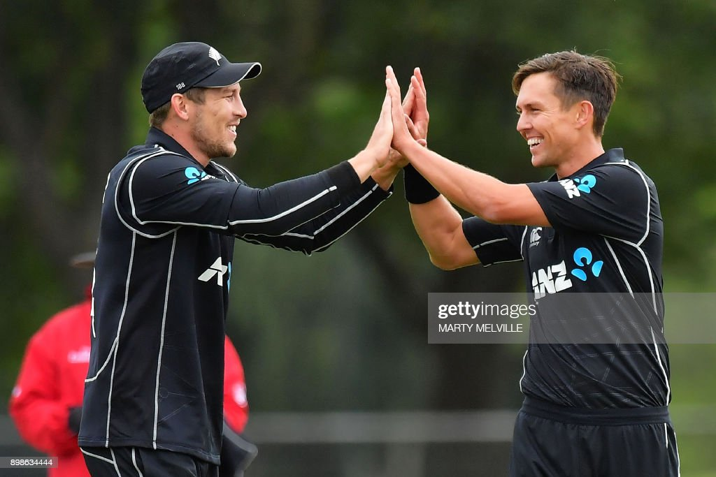 New Zealand's Trent Boult (R) celebrates with teammate George Worker (L) after bowling out West Indies batsman Chadwick Walton during the third one-day international (ODI) cricket match between New Zealand and the West Indies at Hagley Oval in Christchurch on December 26, 2017. / AFP PHOTO / Marty MELVILLE