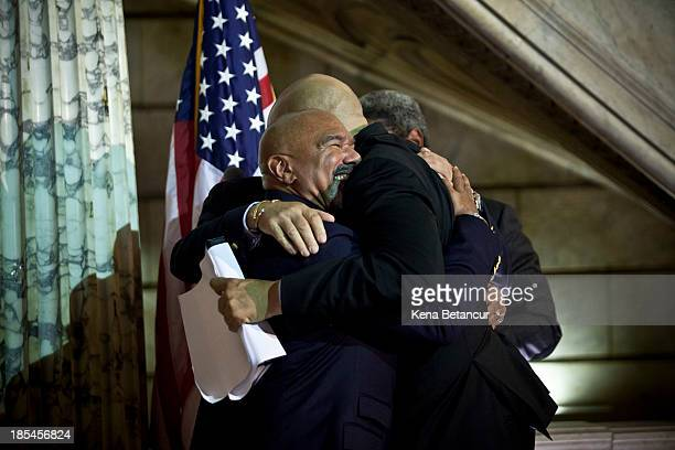 Newark Mayor and newly elected US Senator Cory Booker embraces Joesph Panessidi and Orville Bell after officiating their wedding ceremony at City...