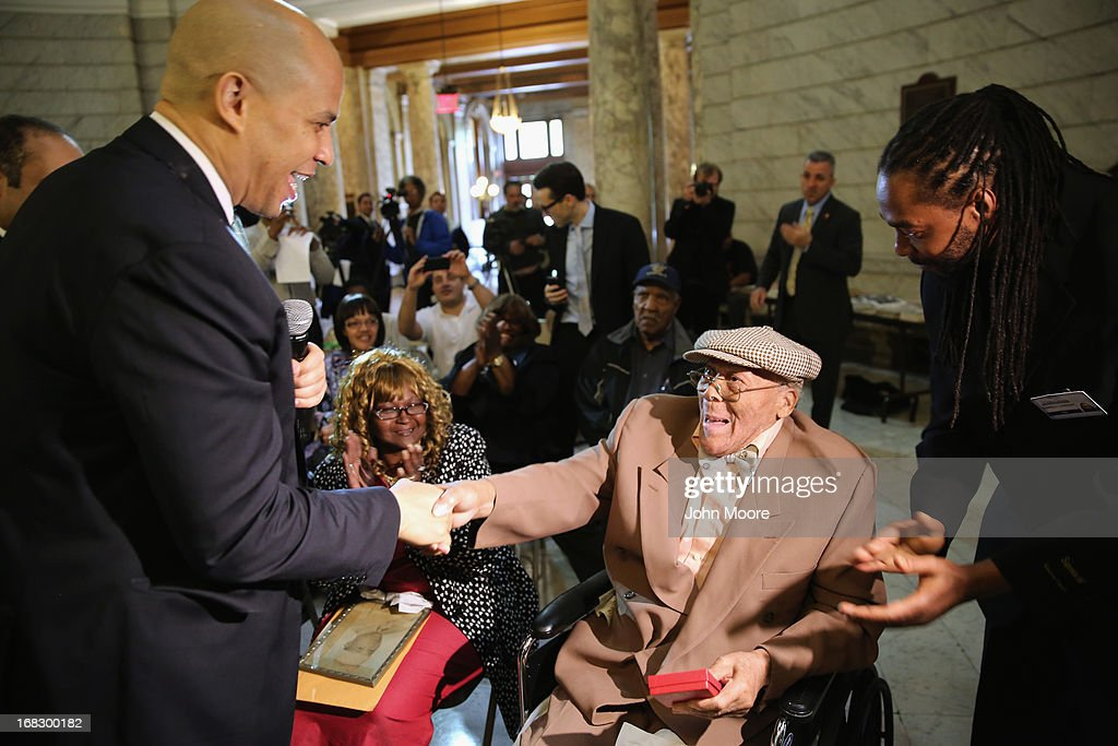 Newark Mayor Cory Booker congratulates 90-year-old WWII veteran Willie Wilkins at the Newark City Hall on May 8, 2013 in Newark, New Jersey. Booker, who has declared that he will run for New Jersey's open U.S. Senate seat in 2014, honored the 90-year-old WWII veteran on the 68th anniversary of Victory in Europe Day. At the ceremony, Wilkins received his dog tags, which were recently unearthed in a French garden, some 67 years after he lost them in France during WWII.