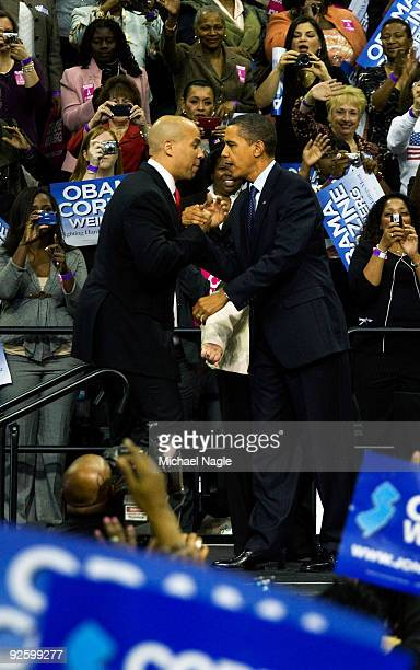 Newark Mayor Cory Booker shakes hands with US President Barack Obama at a campaign rally for New Jersey Gov Jon Corzine at the Prudential Center on...