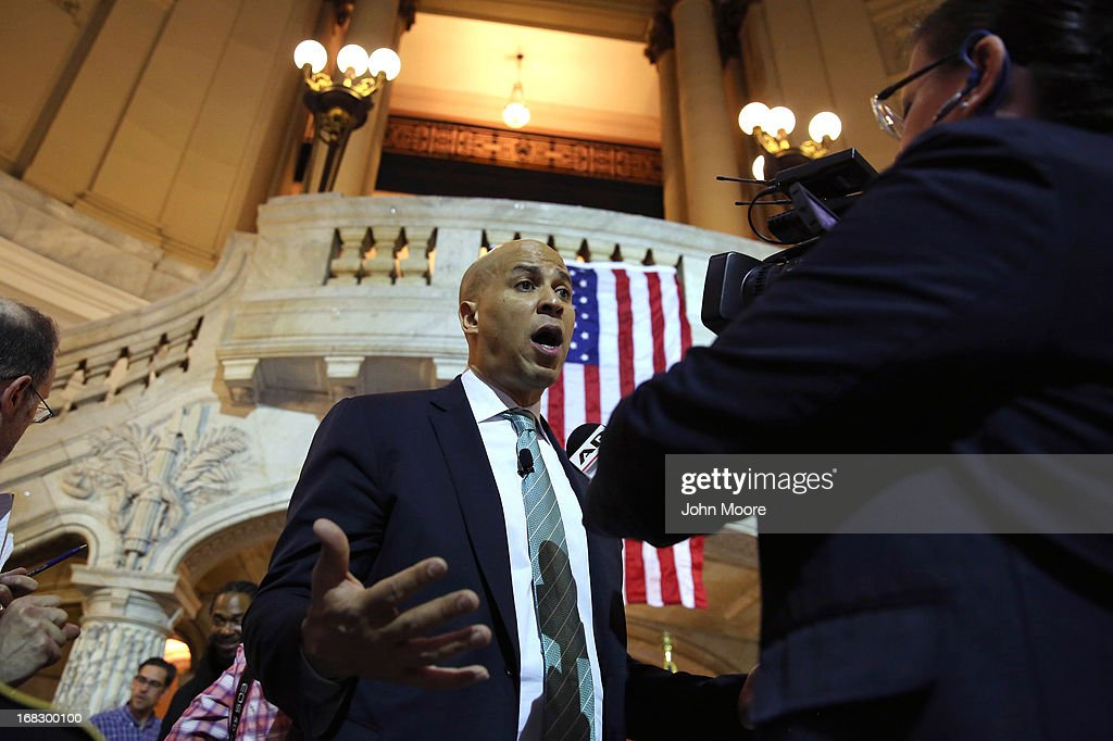 Newark Mayor Cory Booker speaks with a reporter at the Newark City Hall on May 8, 2013 in Newark, New Jersey. Booker, who has declared that he will run for New Jersey's open U.S. Senate seat in 2014, was attending a ceremony honoring 90-year-old WWII veteran Willie Wilkins on the 68th anniversary of Victory in Europe Day.