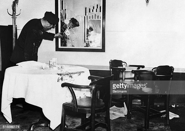 A Newark New Jersey police officer examines a shattered mirror at the scene of the mob assassination of Arthur Dutch Schultz Flegenheimer...