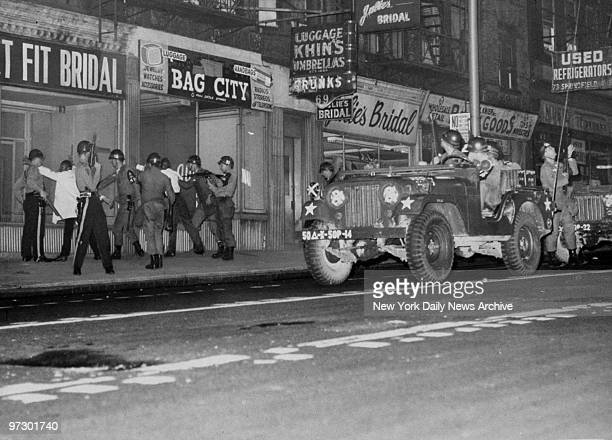 Newark Police and National Guardsmen search for looting suspects outside stores during riots