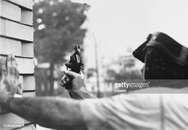 Newark police officer shelters from a sniper during the race riots in Newark, New Jersey, 16th July 1967. The riots were sparked by the beating of...