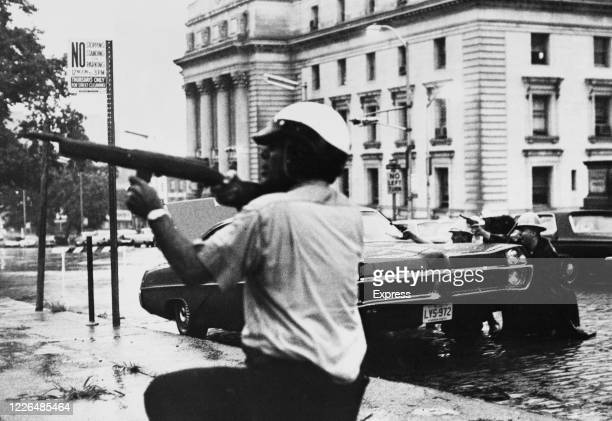 Newark police officers and state troopers exchange fire with a sniper during the race riots in Newark, New Jersey, 16th July 1967. The riots were...
