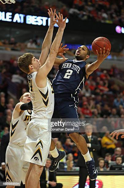 J Newbill of the Penn State Nittany Lions shoots against Adam Woodbury of the Iowa Hawkeyes during the second round of the 2015 Big Ten Men's...