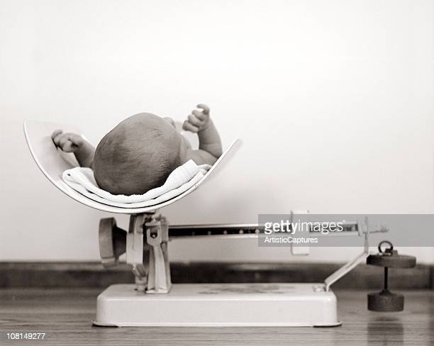 Newborn Baby Being Weighed on Vintage Scale, Black and White