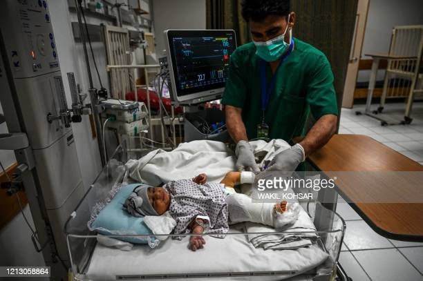 Newborn baby, Bibi Amena, receives treatment for the gun wound in her right leg as she has been rescued and brought to the French Medical Institute...