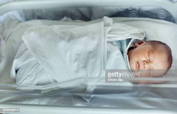 Newborn baby boy asleep in hospital bassinet