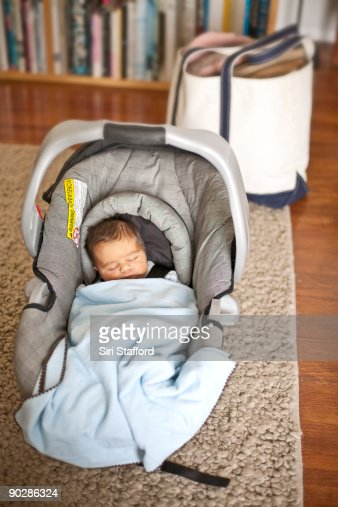 Newborn Baby Boy In Car Seat Carrier Arriving Home Stock