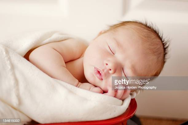 Newborn baby boy in red wagon