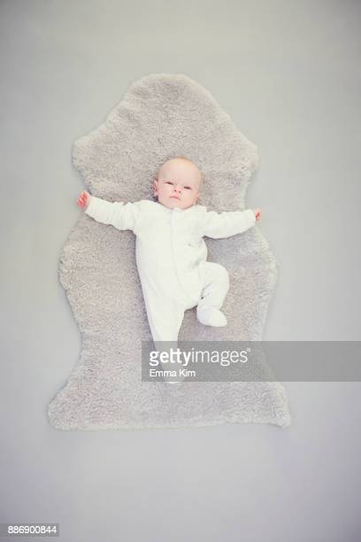 newborn baby boy, lying on rug, overhead view - baby onesie stock photos and pictures