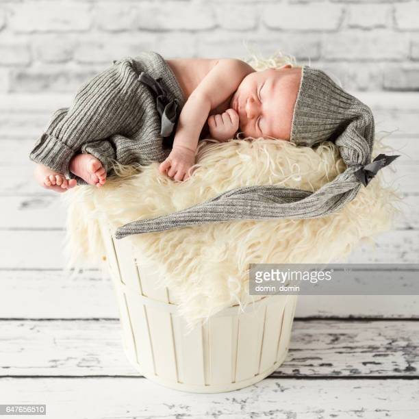 Newborn baby boy sleeping peacefully in wooden washtub, home interior