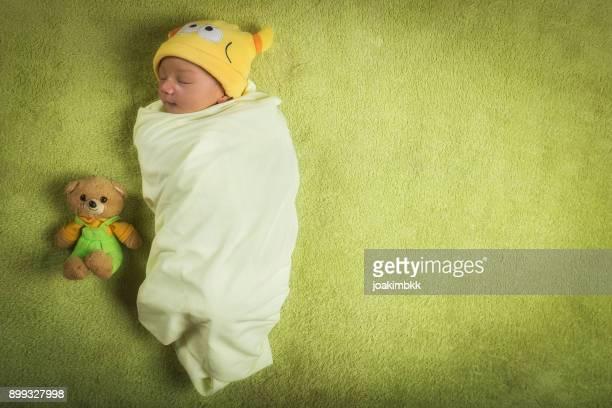 Newborn baby boy wrapped in swaddle with teddy bear