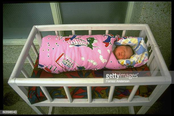 Newborn baby girl asleep in crib at Beijing Maternity Hospital re proposed eugenics law aimed at sick retarded to improve quality of population