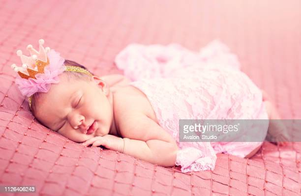 newborn baby girl in a crown is sleeping on a pink bedspread - princess stock pictures, royalty-free photos & images