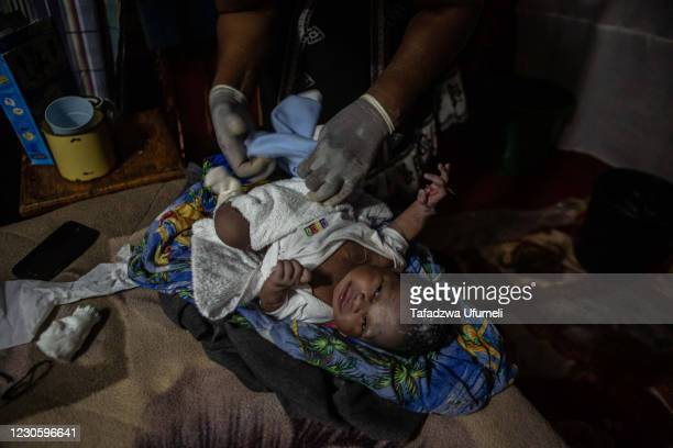Newborn baby girl lies on the bed whilst being dressed by Midwife Ivy Gatsi shortly after being born in early hours of the morning in the delivery...