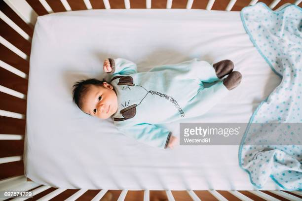 Newborn baby girl lying in crib