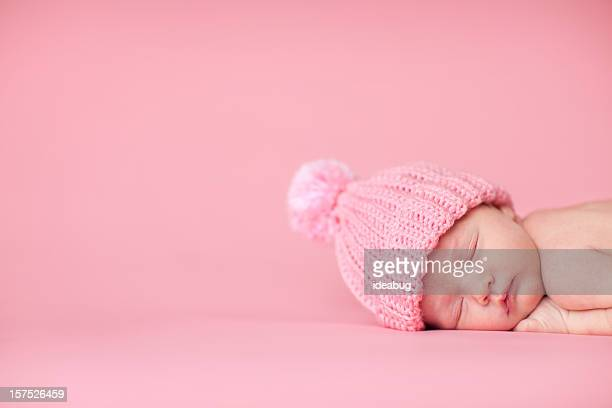 Newborn Baby Girl Sleeping Peacefully on Pink Background