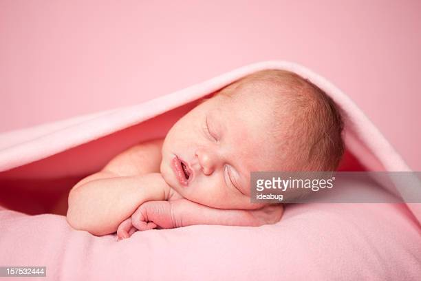 Newborn Baby Girl Sleeping Peacefully Under a Pink Blanket