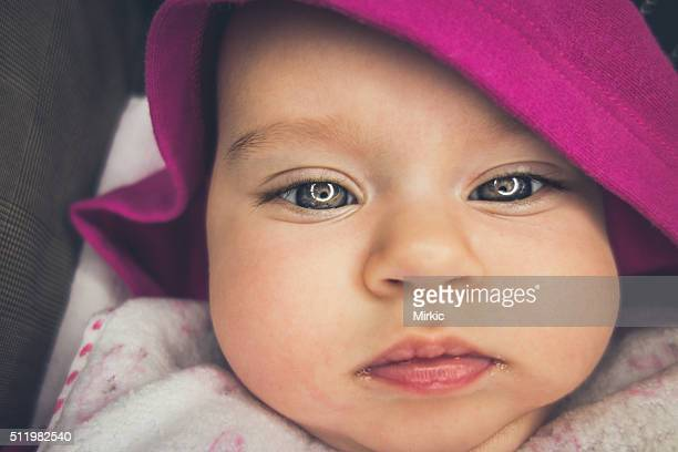 Newborn baby girl with a hood portrait