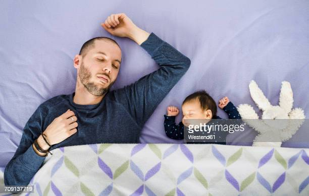 Newborn baby girl,father and a stuffed rabbit sleeping in bed