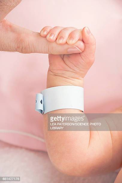 Newborn baby gripping parents finger